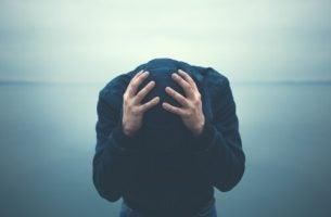 Man die met zijn handen op zijn hoofd voorover gebogen staat omdat hij een van die mensen met angstgevoelens is