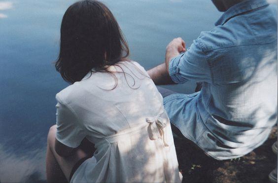 Jongen en een meisje die aan het water zitten en elkaar emotionele steun bieden