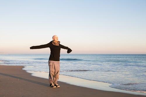 Vrouw met kanker die op het strand geniet van de frisse lucht