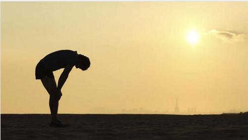 Man die uitgeput van het rennen voorover gebogen staat