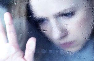 Vrouw die droevig uit het raam kijkt omdat ze er genoeg van heeft om schreeuwen als communicatiemiddel te gebruiken