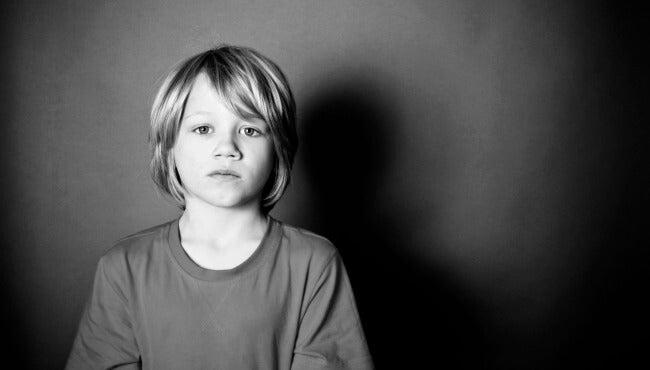 Jongetje dat voor een zwarte achtergrond staat en droevig voor zich uit kijkt als voorbeeld van die vergeten kinderen