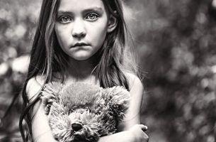 Meisje met een bos bloemen in haar handen eenzaam voor zich uit kijkt als voorbeeld van vergeten kinderen