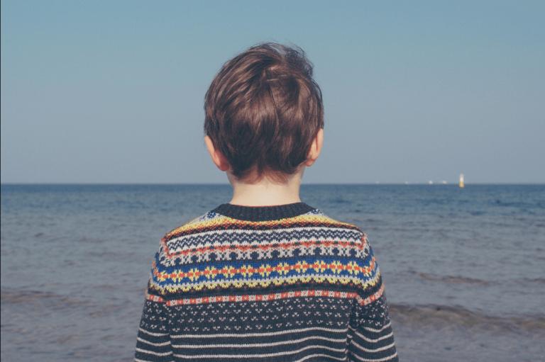 Eenzaam jongetje aan de zee