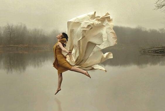 Vrouw die vrijuit op een meer danst, als voorbeeld van hoe het leven zou moeten worden geleefd volgens de slow-movement