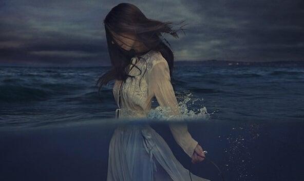 Vrouw in de zee die zich overweldigd voelt door verdriet