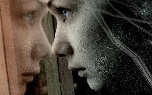Vrouw die door een raam kijkt en wiens gezicht wordt weerspiegeld in ditzelfde raam