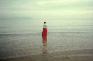 Vrouw kijkt uit over oceaan en denkt na over al die dappere mensen in haar leven