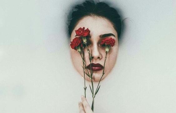 Vrouw met rode anjers op haar ogen die last heeft van een van die emotionele katers