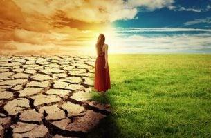 Vrouw die op de grens tussen groen gras en droge aarde staat als symbool voor de grens tussen leven en dood, waar sommige mensen met kanker op staan