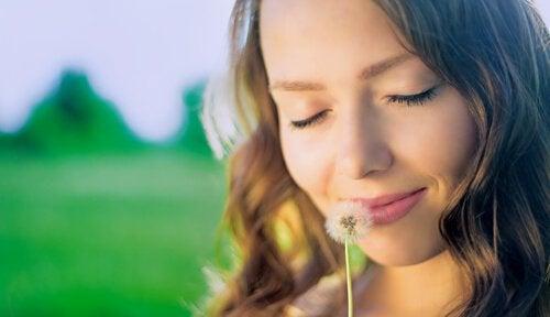 Vrouw ruikt aan bloem, heeft innerlijke rust gevonden en kan hierdoor vooruitkomen in het leven