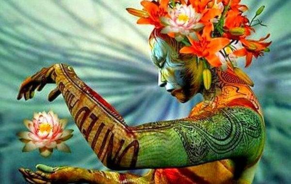 Vrouw die kleurrijk versierd is met bodypaint en een lotus tussen haar handen vasthoudt