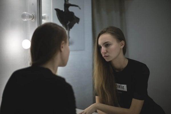Meisje dat ontevreden naar zichzelf kijkt in de spiegel