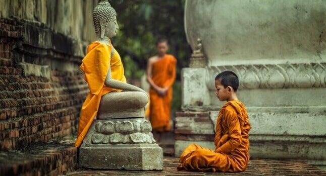 Boeddhistische monnik die mediteert bij een beeld van Boeddha