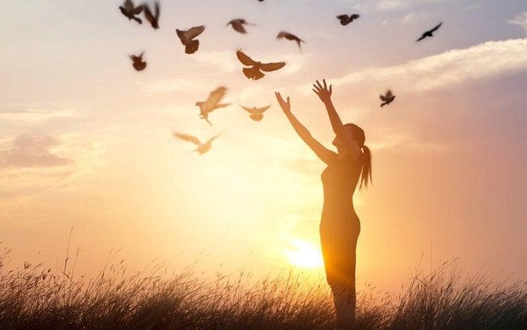 Vrouw die vogels vrijlaat bij zonsondergang