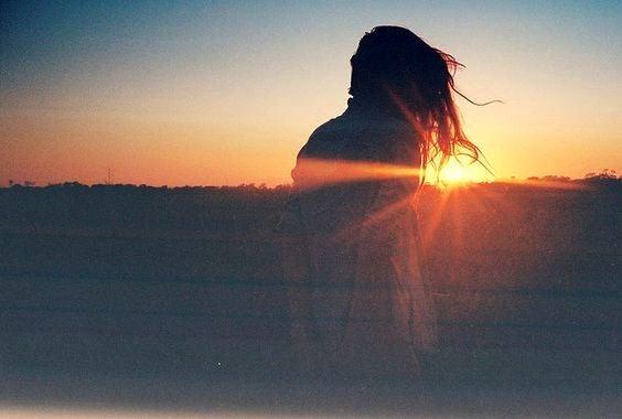 Vrouw die naar de ondergaande zon kijkt