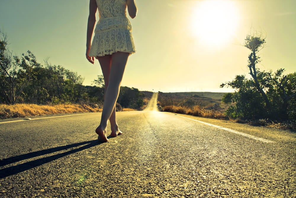 Meisje dat op blote voeten over een geasfalteerde weg loopt