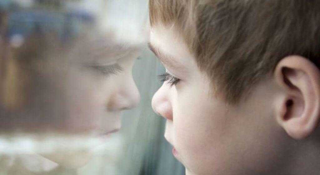 Jongetje dat verdrietig uit het raam kijkt