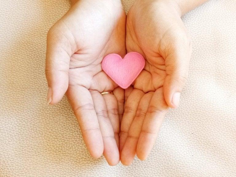 Een klein roze hartje in de handen van een vrouw