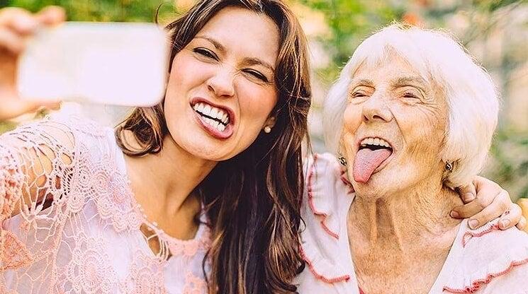 Een oudere vrouw die samen met een jongere vrouw een gekke bek trekt