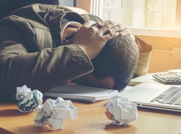 Man die uit frustratie zijn hoofd op tafel legt, want omgaan met negatieve mensen kan zeer frustrerend zijn