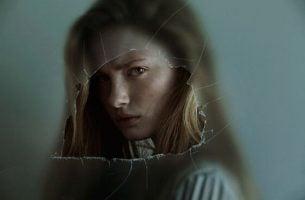 Meisje dat boos kijkt door een gat in een raam, want haar emoties beheersen is moeilijk voor haar
