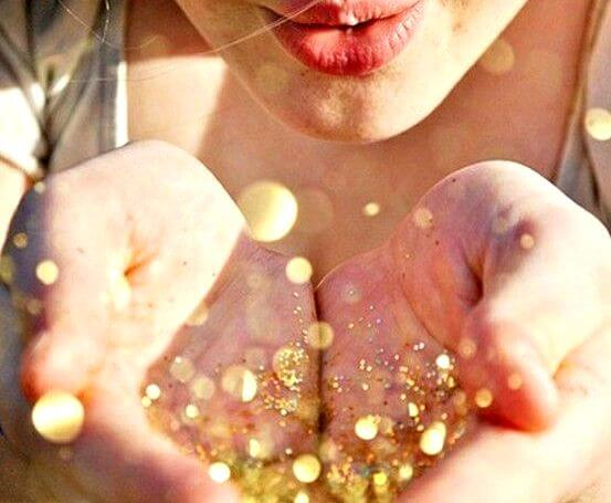 Vrouw die goud glitter uit haar handen blaast