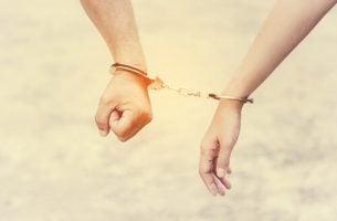 Twee mensen die aan elkaar vastzitten met handboeien als voorbeeld van codependency