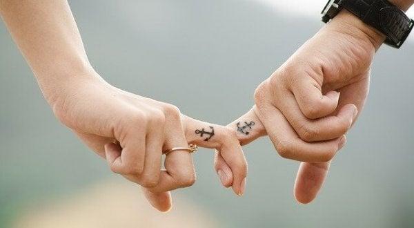 Handen met tattoos van ankers die elkaar wanhopig vasthouden, als symbool voor de afhankelijke persoonlijkheidsstoornis