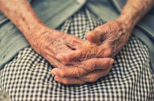 De handen van een oude vrouw wiens familie moet leren omgaan met dementie