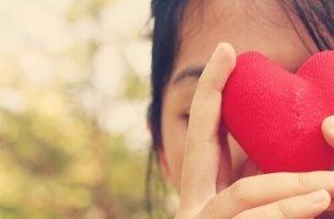 Meisje dat een hartje voor haar ogen houdt, want ze weet dat niet van jezelf houden schadelijk kan zijn