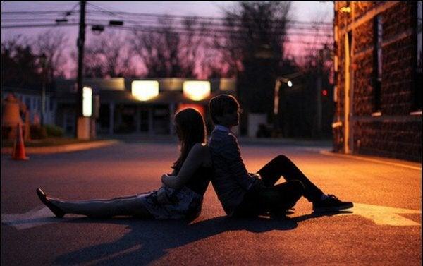 Jong stel dat met hun ruggen tegen elkaar op een geasfalteerde weg zitten en denken: niemand houdt van mij