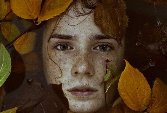 Gezicht van een jongen tussen bladeren