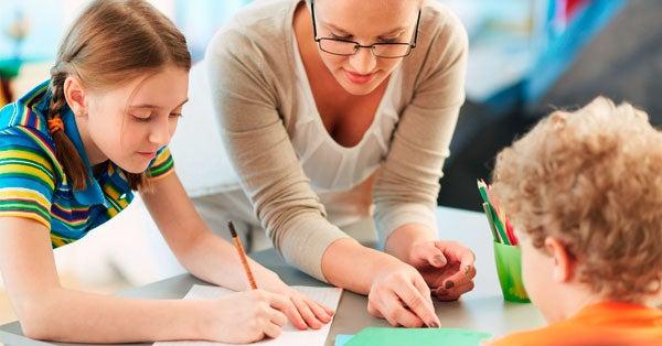 Een lerares die twee leerlingen helpt
