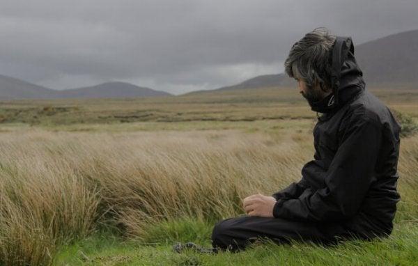 Man die op een winderige dag in de duinen zit