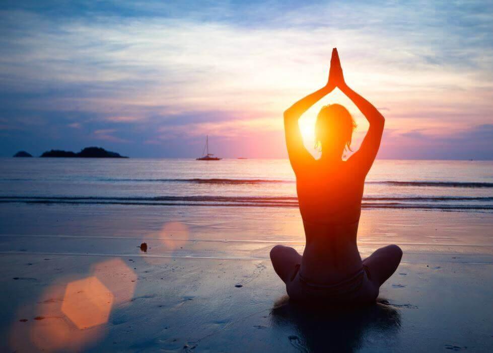 Vrouw die aan het mediteren is op het strand