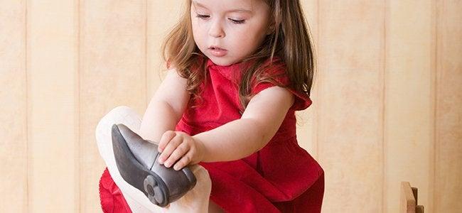Een klein meisje dat haar schoenen aandoet