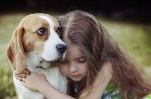 Meisje dat geniet van de liefde van honden door een hond te knuffelen