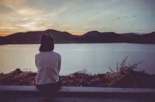 Meisje dat aan de rand van een meer zit, want zij wil lijden vermijden en door de pijn heen groeien