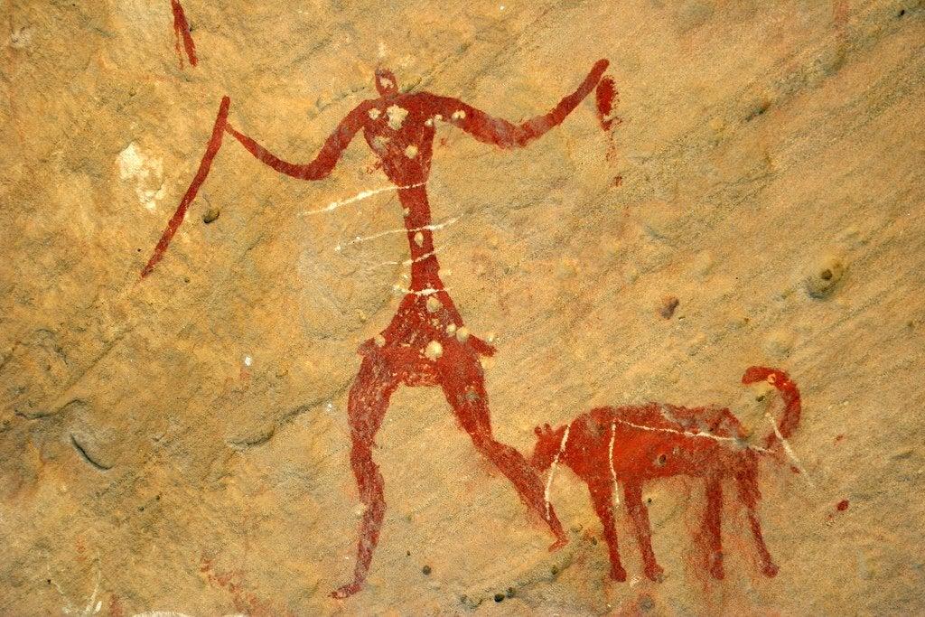 Een grotschildering van een man en een hond