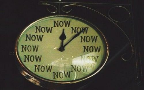 Klok waarop in plaats van cijfers twaalf keer het woord 'nu'staat, je leven veranderen kan op elk moment.