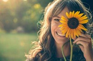 Een van die positieve mensen die een zonnebloem voor haar oog houdt