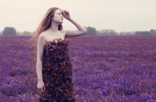 Vrouw die in een veld vol paarse bloemen staat en door zware tijden gaat