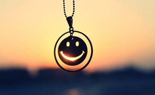 Een ketting met daaraan een smiley: je moet leren lachen om jezelf