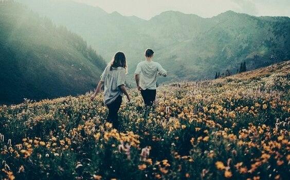 Jongen en een meisje die samen door een vallei lopen die vol bloemen staan