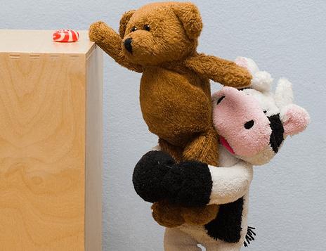 Knuffelkoe die een knuffelbeer helpt