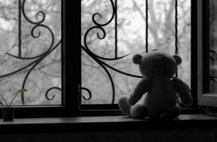Zwart-witte foto van een verlaten teddybeer op een vensterbank als symbool voor pathologische rouw