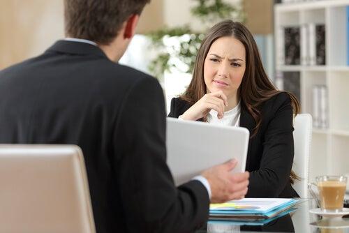 Vrouw die een gesprek heeft meteen collega en aan zichzelf twijfelt