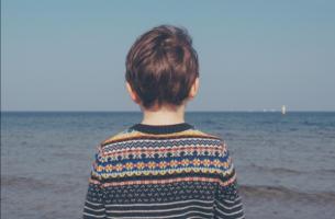 Verdriet en rouw bij kinderen te zien bij een kind dat over de zee uitkijkt