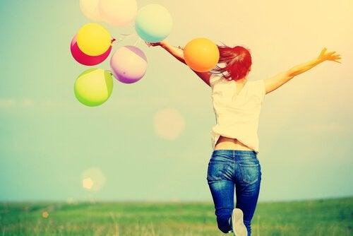 Gelukkige vrouw met kleurrijke ballonnen, maar om geluk te vinden moet je soms een risico nemen